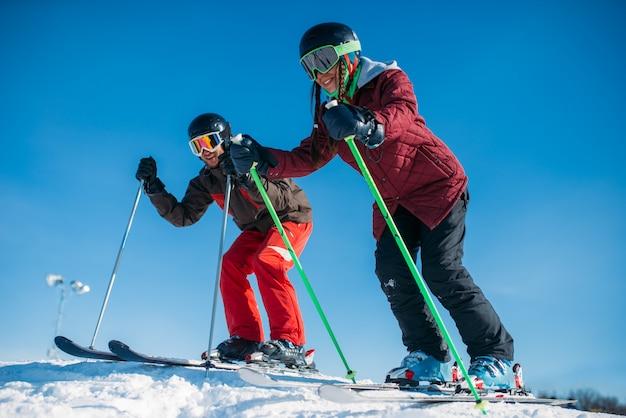 Esquiadores masculinos y femeninos corriendo desde la montaña, vista lateral. deporte activo de invierno, estilo de vida extremo. esquí alpino