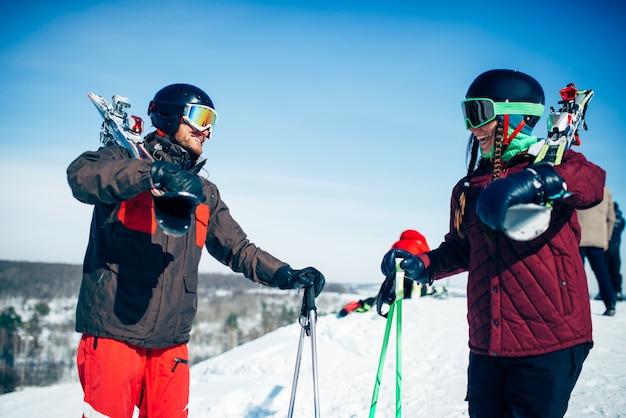 Esquiadores masculinos y femeninos posa con esquís y bastones