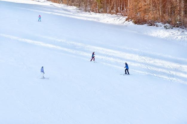 Los esquiadores montan en la ladera cubierta de nieve. en la distancia