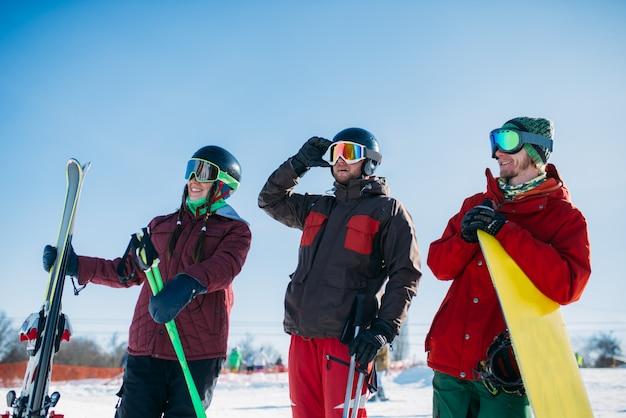 Esquiadores y snowboarder posan juntos, deporte activo de invierno. esquí de montaña, snowboard, estilo de vida extremo