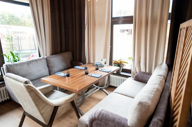 Esquina de un acogedor restaurante o cafetería con cómodos sofás y sillón alrededor de la mesa servida entre las ventanas