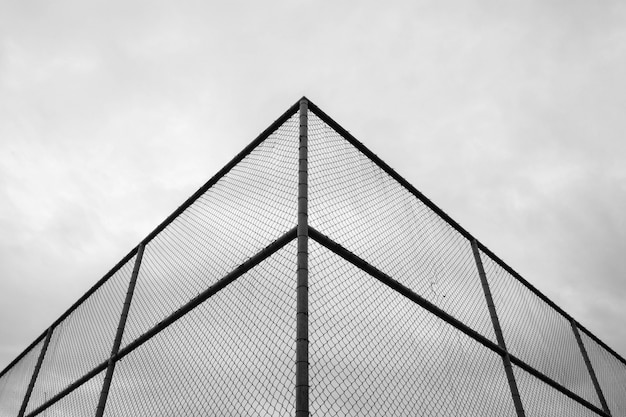 Esquina de alambre de jaula de metal en la cancha de tenis