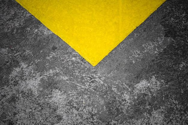 Esquina de un amarillo pintado en la textura del piso de concreto - fondo