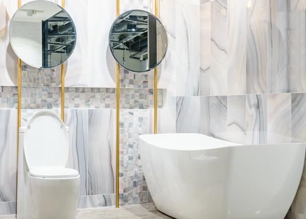 Esquina de baño blanca y de madera con una bañera blanca, un inodoro y un estante incorporado