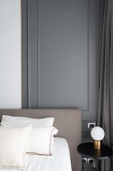 Esquina del dormitorio decorada con molduras pintadas con spray gris estilo clásico moderno con lámpara de mesa dorada en mesa auxiliar de madera negra