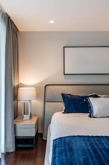 Esquina de dormitorio elegante con cabecera de tela gris y cama con almohadas suaves con paredes pintadas de azul marino y blanco en el fondo / diseño interior acogedor / interior moderno