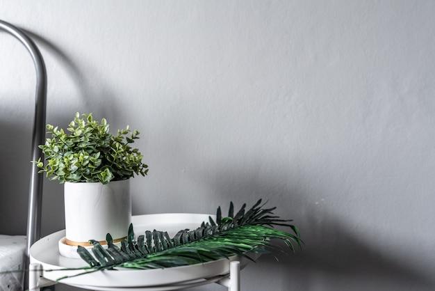 Esquina del dormitorio con plantas artificiales en maceta de mármol de cerámica blanca en la mesa auxiliar en estilo escandinavo moderno
