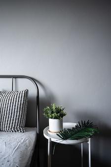 Esquina del dormitorio con plantas artificiales en pintura de mármol blanco de cerámica sobre mesa auxiliar de metal blanco en estilo escandinavo moderno
