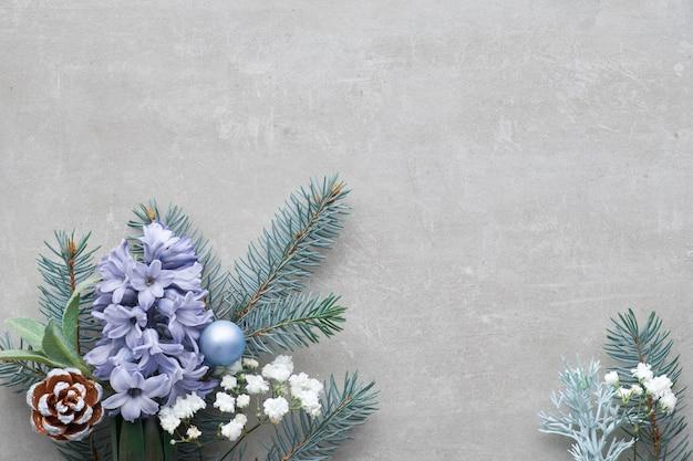 Esquina floral de invierno en verde y azul con ramas de abeto, flores de jacinto y hojas sobre fondo de hormigón