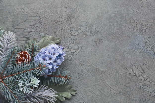 Esquina floral de invierno en verde y azul con ramas de abeto, flores de jacinto y hojas sobre fondo verde