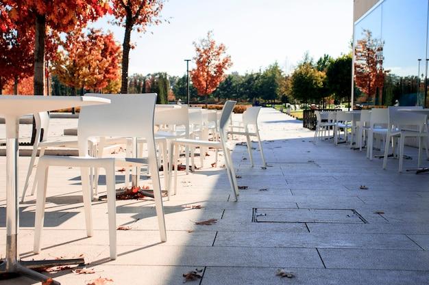 Esquina del jardín en otoño. veranda romántica, terraza rústica. terraza de café antiguo, café de la calle. diseño de interiores moderno