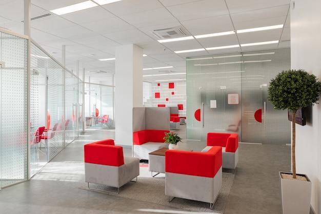 Esquina de la oficina moderna con paredes blancas, piso gris, área de espacio abierto con sillones rojo-blanco y habitaciones detrás de una pared de vidrio.