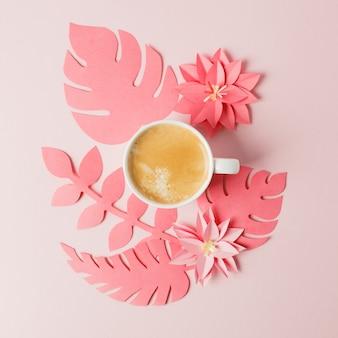 Esquina de la planta artesanal de papel colar vivo con hojas tropicales y café.