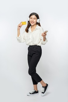 Estaba vestida con una camisa blanca y pantalón oscuro para ir de compras y sostener una tarjeta de crédito y un teléfono inteligente.