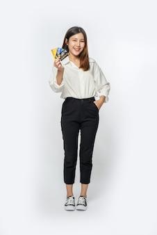 Estaba vestida con una camisa blanca y pantalón oscuro para ir de compras y sostener una tarjeta de crédito.