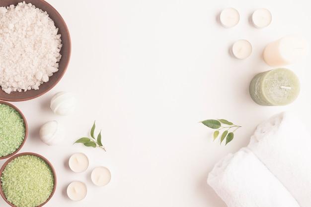 Establecido para tratamientos de spa con sal aromática y velas en el fondo