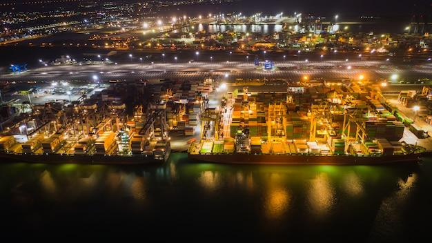Estación de carga para la exportación internacional e importación por barco con contenedores en alta mar por la noche.