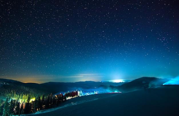 Estación de esquí nocturna europea con vapor y humo.