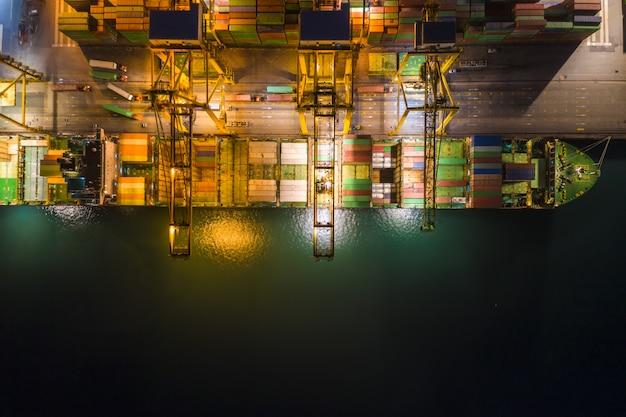 La estación internacional de carga marítima en grandes contenedores de carga se envía por encima de la vista desde la cámara del avión no tripulado en la noche