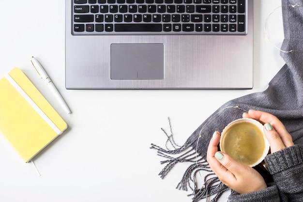 Estación de trabajo de otoño con laptop, planeador, bolígrafo y taza de café con manos femeninas