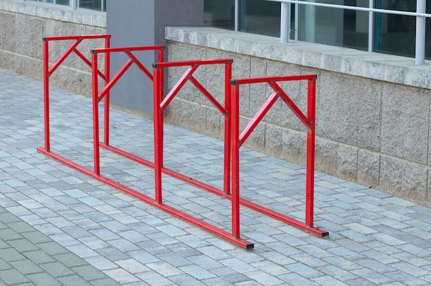 Estacionamiento de acero o hierro rojo para bicicletas de pie sobre pavimento gris en edificio de oficinas o apartamentos