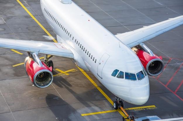 Estacionamiento de aviones comerciales en el aeropuerto iluminado por el sol, vista superior.