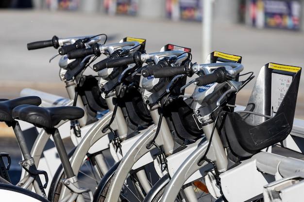 Estacionamiento en la calle con bicicletas con canastas para alquilar bajo el sol brillante