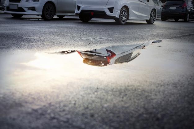 Estacionamientos mojados después de una fuerte lluvia caen con reflejo del cielo en un charco en el suelo. enfoque selectivo.
