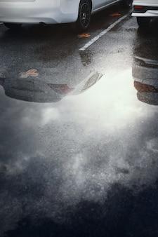 Estacionamientos mojados después de una fuerte lluvia caen con reflejo del coche en un charco en el suelo. enfoque selectivo.