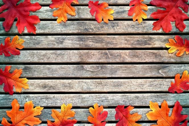 Estaciones, fondo y concepto de la textura - hojas coloridas del otoño en un fondo de madera.