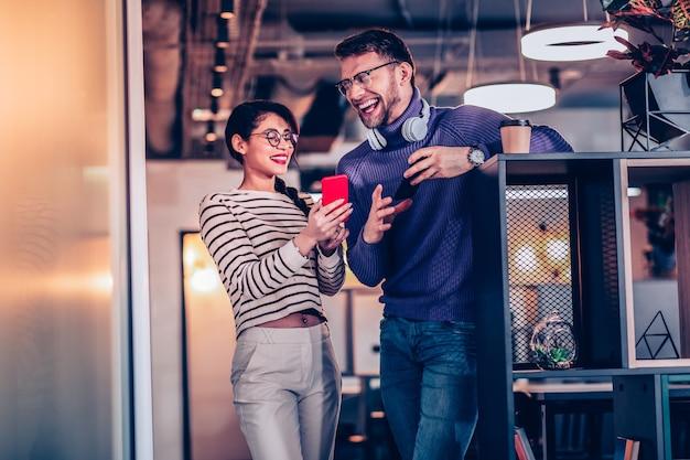 Estado de ánimo alegre. amable chica de pelo largo sosteniendo el teléfono en la mano derecha mientras está de pie cerca de su pareja