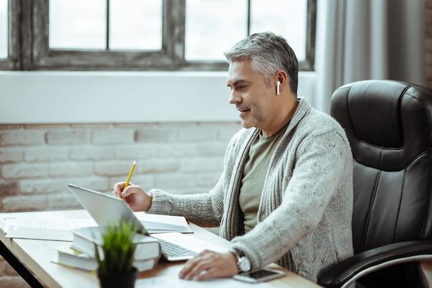 Estado de ánimo alegre. hombre feliz positivo sonriendo mientras mira la pantalla del portátil