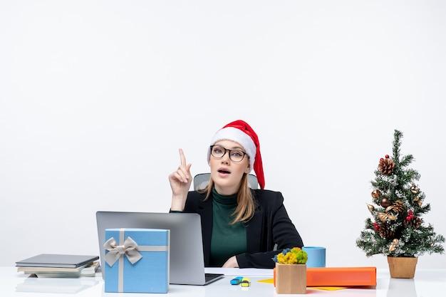 Estado de ánimo de año nuevo con mujer decidida con un sombrero de santa claus sentado en una mesa con un árbol de navidad y un regalo sobre fondo blanco