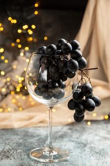 Estado de ánimo de año nuevo con uva negra en un vaso y una toalla de color nude sobre fondo oscuro
