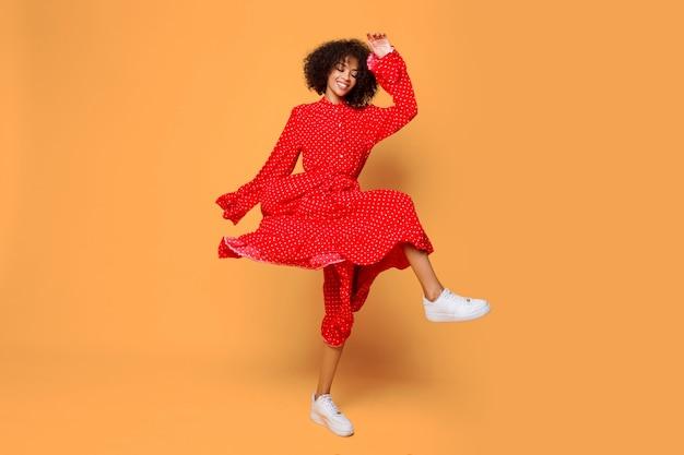 Estado de ánimo de ensueño. chica africana con estilo bailando y saltando en naranja