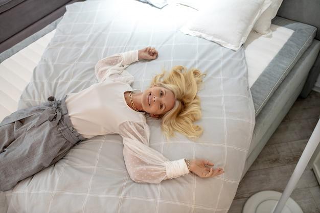 Estado de ánimo maravilloso mujer con cabello rubio en una blusa blanca está acostada en una cama grande y cómoda, sonriendo feliz.