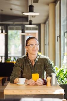 Estado de ánimo perfecto. buen hombre positivo disfrutando de su día mientras está sentado a la mesa en el café