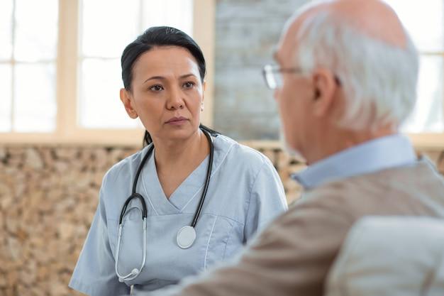 Estado de salud. médico serio profesional vistiendo uniforme mientras consulta a un hombre mayor y posando sobre fondo borroso