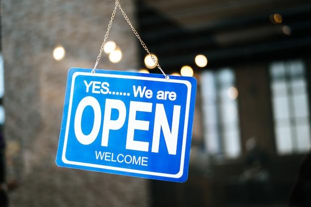 Estamos abiertos, firme a través del cristal de la ventana en el restaurante