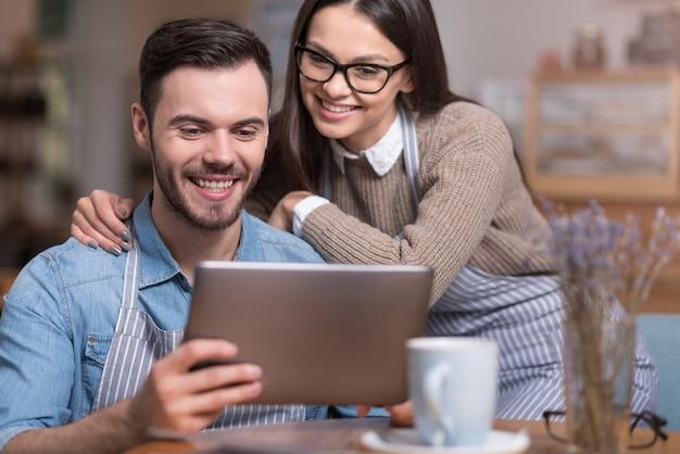 Estamos felices juntos. hermosa mujer joven y agradable guapo sonriendo y usando tableta mientras está sentado en la mesa.