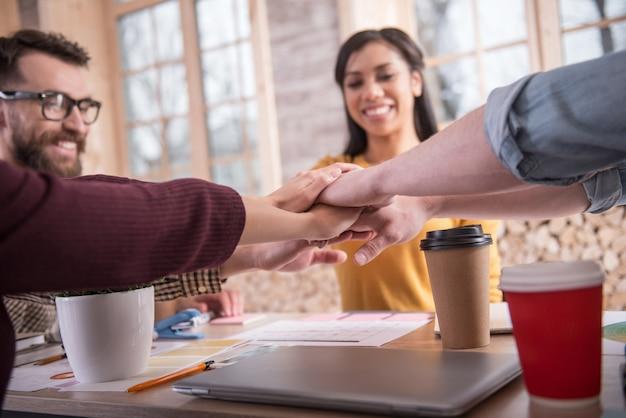 Estamos juntos. manos de agradables personas positivas alegres que se juntan mientras muestran su unidad