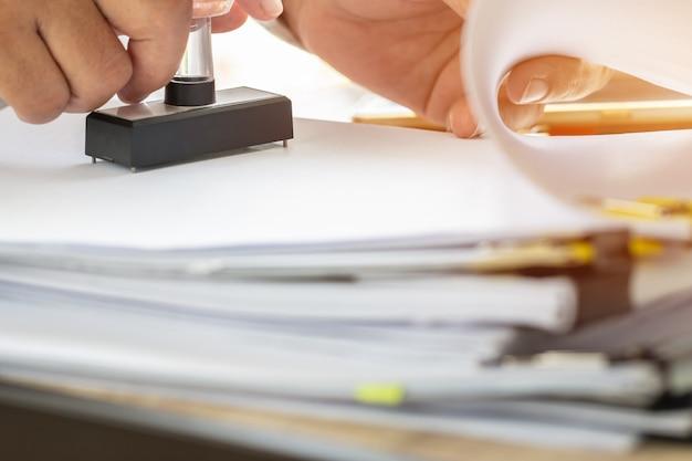 Estampado de manos de la persona de negocios en el formulario de solicitud aprobado