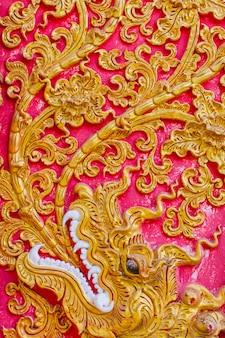 El estampado de plores tailandés grabó en relieve la pintura del cemento con oro y el fondo del color rojo en templo.