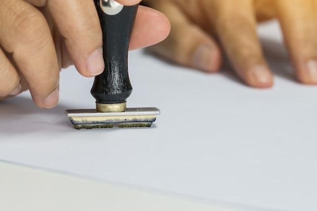Estampilla de mano de la persona en papel de formulario de solicitud aprobado en la oficina de escritorio