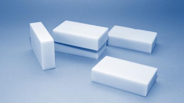 Estandarte con esponja doméstica de melamina para limpiar sobre fondo azul en tonos de color azul clásico de moda del año 2020.