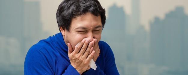 Estandarte del hombre asiático con la mascarilla contra la contaminación del aire en el balcón.