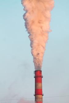 Estandarte vertical de chimeneas industriales con un intenso humo rosa al atardecer que causa la contaminación del aire en el cielo azul
