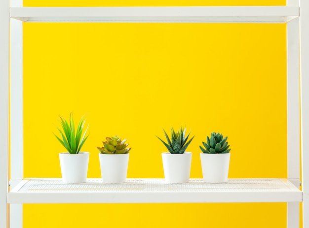 Estante blanco con objetos de papelería contra la pared amarilla brillante