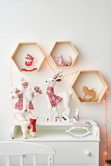 Estante con figuras de navidad santa y ciervos en la habitación de los niños. interior de navidad de la habitación de los niños.navidad en la guardería.