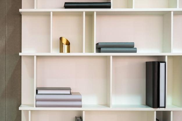 Estante interior de madera blanca con diferentes objetos relacionados con el hogar.